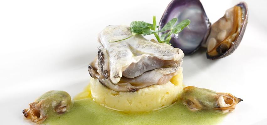 Kokotxas de merluza sobre patata rota y salsa verde de almejas al txakoli