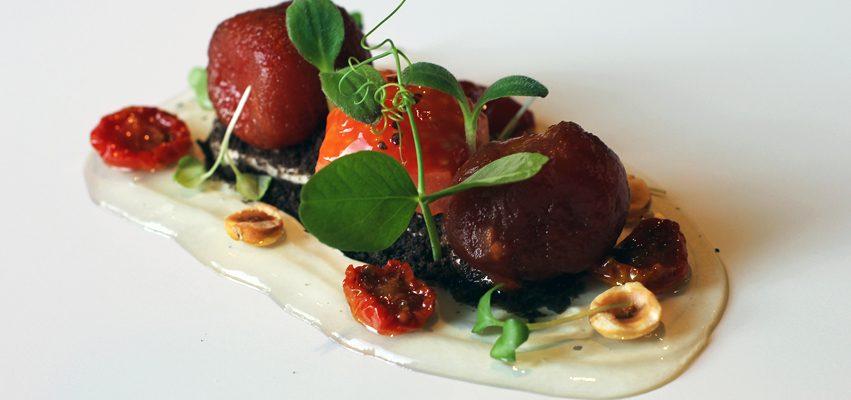 Tomates en texturas sobre antxoas y olivas negras