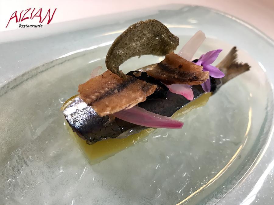 Lomo de sardina sobre gel de aceite a la brasa cebolla morada encurtida ajo negro y espinas crujientes aizian